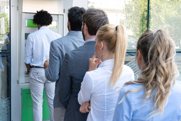 group of people in line at atm - banks and atms stock pictures, royalty-free photos & images