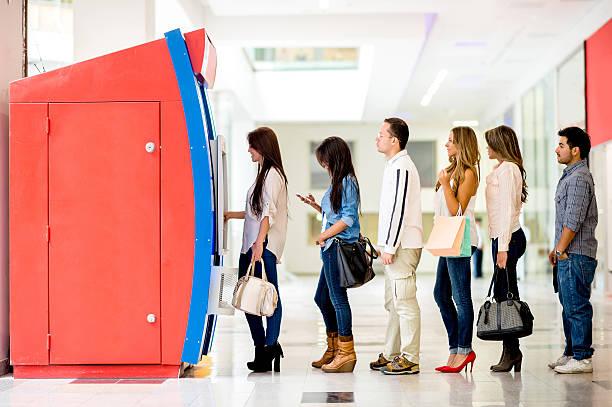 groupe de personnes en ligne pour le distributeur automatique de billets - queue photos et images de collection