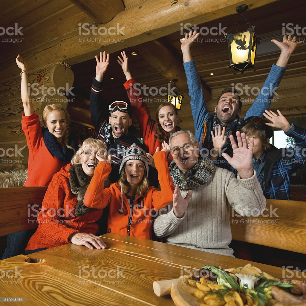Group of people in mountain restaurant An excited multi-generation family sitting in a mountain restaurant after skiing and laughing with raised hands. Active Seniors Stock Photo