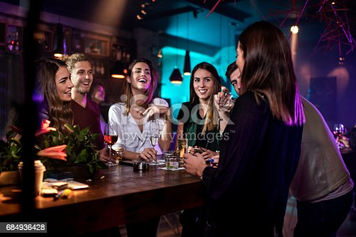 Group of people in the bar having having drinks and fun at night out.