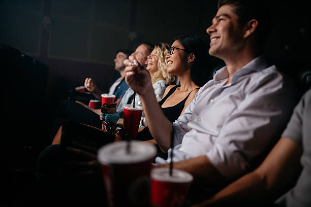 group of people in theater with popcorn and drinks - 映画館 ストックフォトと画像