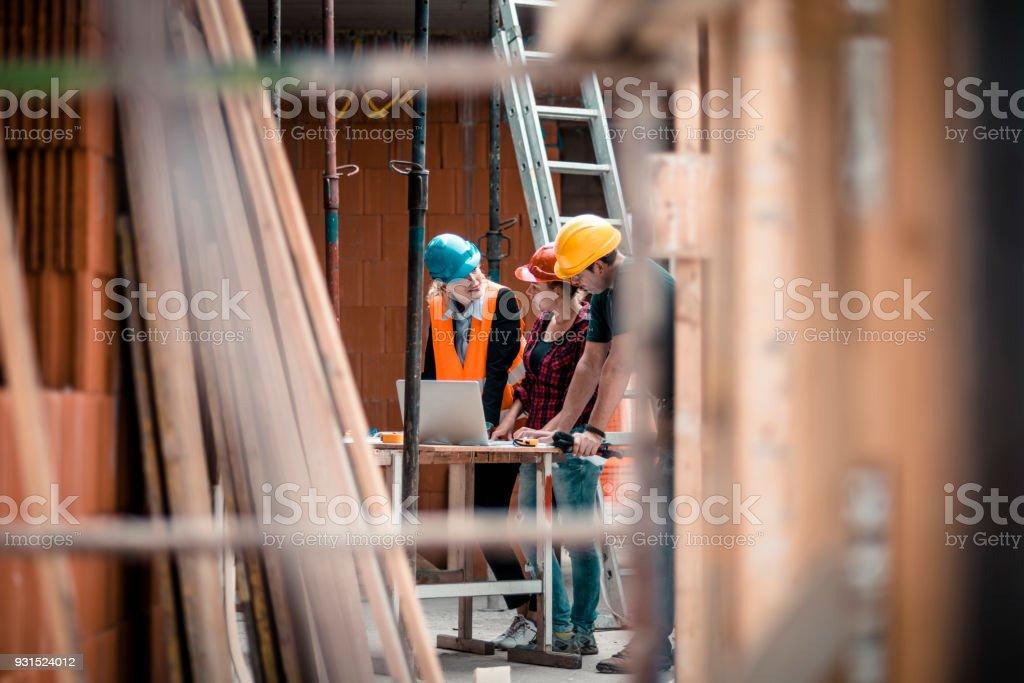 Eine Gruppe von Menschen prüft Pläne für den Bau – Foto