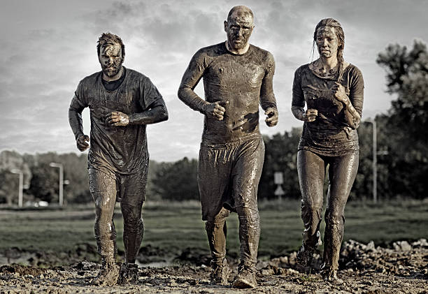 group of people jogging in mud - obstacle run stockfoto's en -beelden