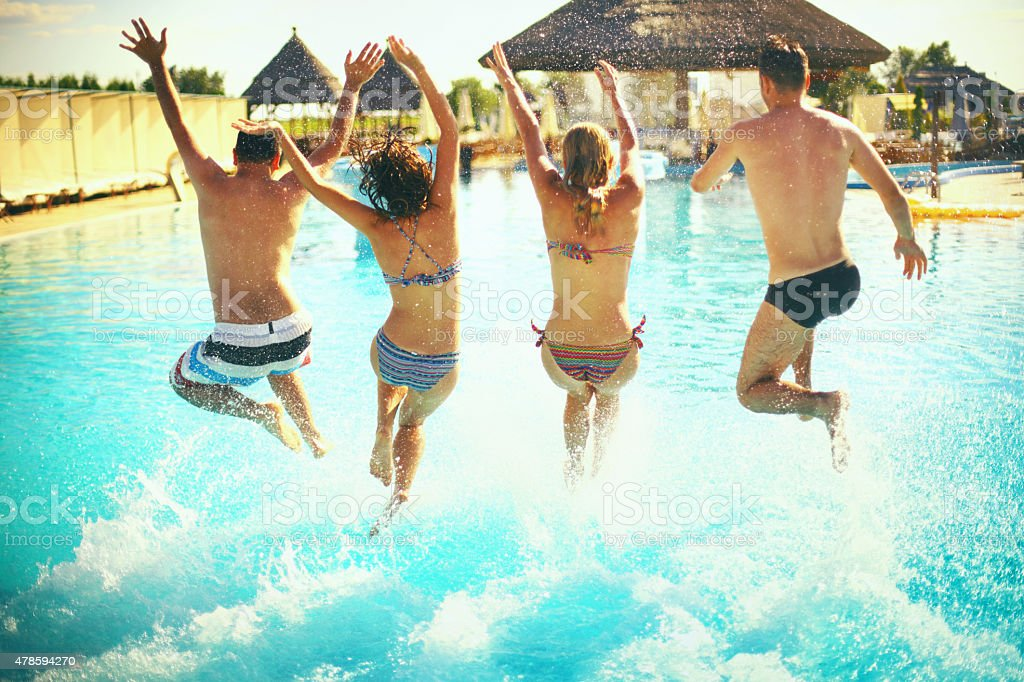 Group of people juming in swimming pool. stock photo