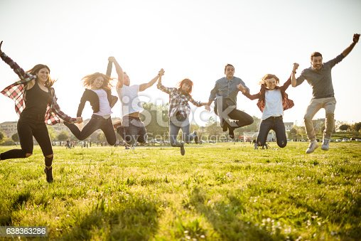 istock Group of people jumping on the park at dusk 638363286