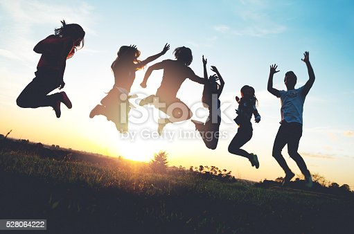 istock Group of people jumping outdoors; sunset 528064222