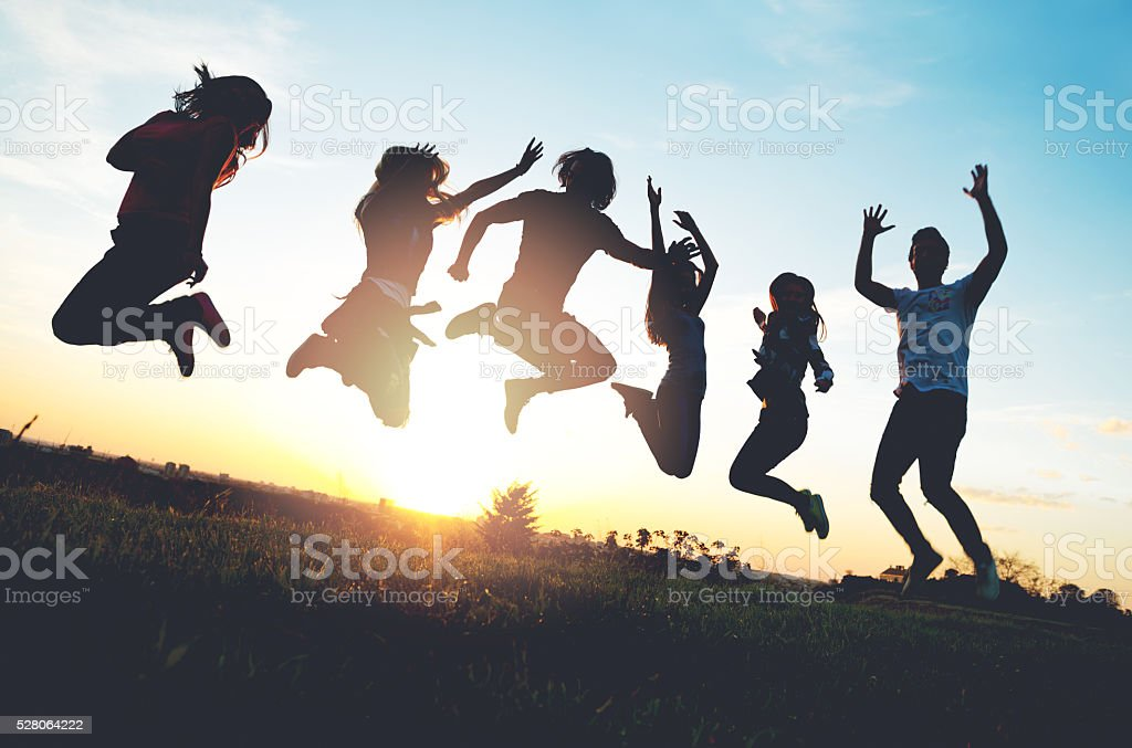 Group of people jumping outdoors; sunset stock photo
