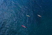Group of unrecognizable people kayaking in ocean, aerial view.