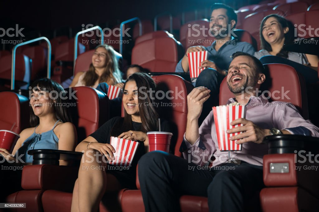 Group of people laughing at the movie theater stock photo
