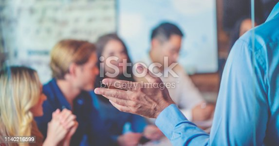 618851838 istock photo Group of people listening to a presentation. Defocussed with focus on foreground. 1140216599