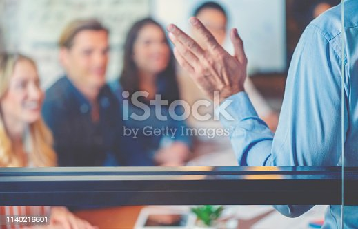 618851838 istock photo Group of people listening to a presentation. Defocussed with focus on foreground. 1140216601