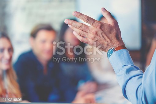 618851838 istock photo Group of people listening to a presentation. Defocussed with focus on foreground 1140216605