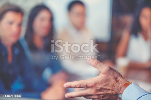 1069233370 istock photo Group of people listening to a presentation. Defocussed with focus on foreground 1140216606