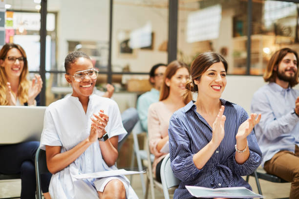 Group of people listening to a presentation speech. Businessman relocating to a new office. Made in Barcelona, Spain. adult learning stock pictures, royalty-free photos & images