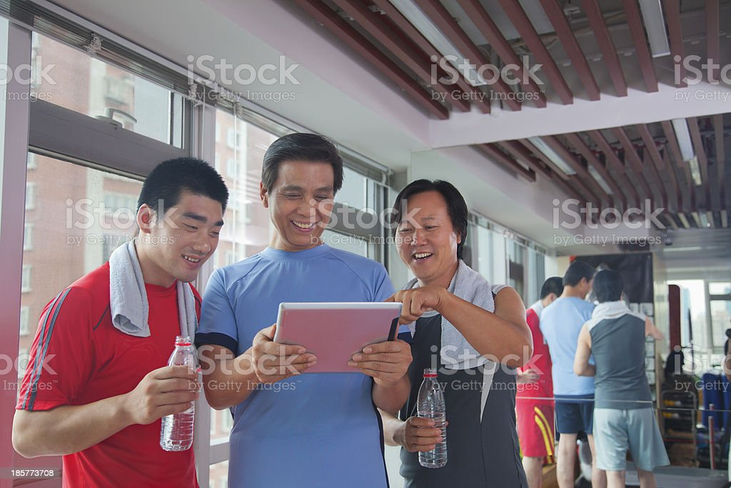 Group of people looking at digital tablet in the gym royalty-free stock photo