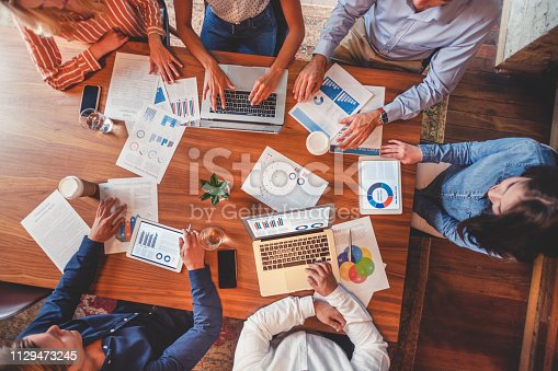 Group of people meeting with technology. There are marketing and strategy documents on the table. There is paperwork on the table with financial graphs, charts and data. There are also technology on the wooden conference table, including laptop computers, digital tablets and mobile phones. Shot from above.