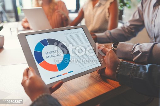 Group of people meeting with technology. Close up of digital tablet with market analysis data on the screen. Multi ethnic group including Caucasian and African American