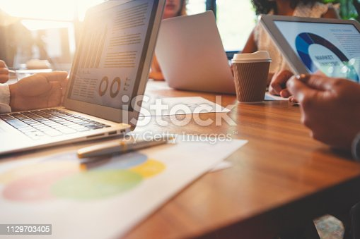 Group of people meeting with technology. There are marketing, financial and strategy documents on the wooden table and on the computers and digital tablets. Multi ethnic group including Caucasian and African American
