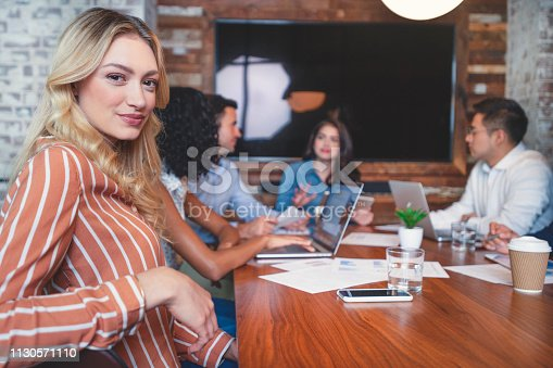 istock Group of people meeting with technology. The female manager is looking at the camera. 1130571110