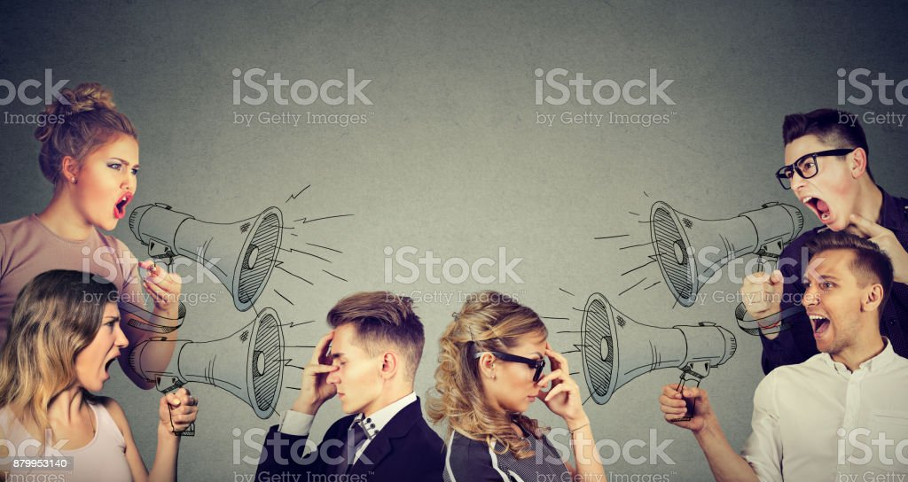 Group of people men and women screaming in megaphones at sad depressed young couple stock photo