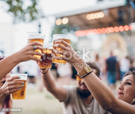 Group of four friends toasting with beer on a music festival