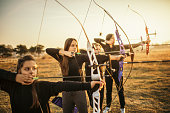 Group of females on outdoors archery training at sunset. They are all aiming with bow and arrow. The group includes mid adult women, children, teenagers