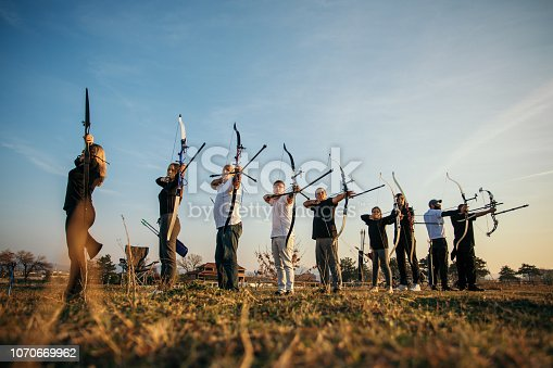 Large group of people on outdoors archery training at sunset. Theay are all aiming with bow and arrow. The group includes men, women, seniors, children, teenagers