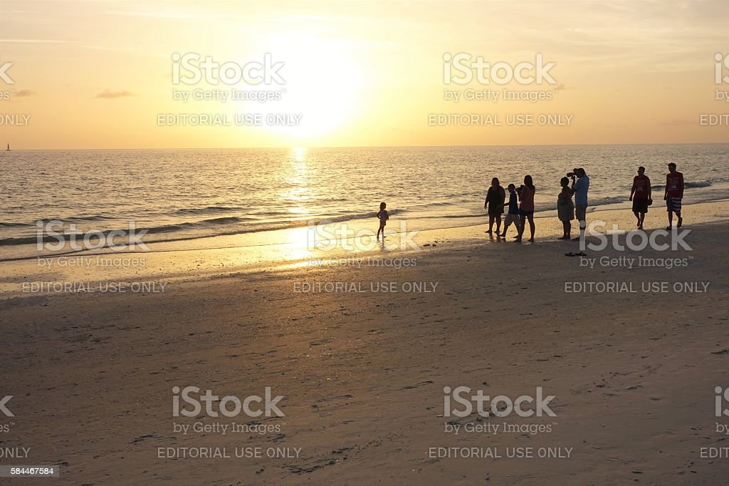 Group of people on beach at sunset stock photo