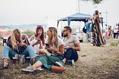 Group of friends sitting on ground and having fun on a music festival