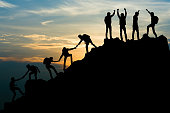 Group of people on peak mountain climbing helping team work , travel trekking success business concept