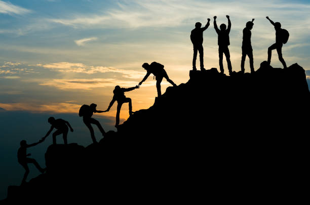Group of people on peak mountain climbing helping team work , travel trekking success business concept stock photo