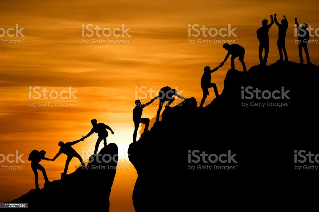 Group of people on peak mountain climbing helping team work , travel trekking success business concept Group of people on peak mountain climbing helping team work , travel trekking success business concept A Helping Hand Stock Photo