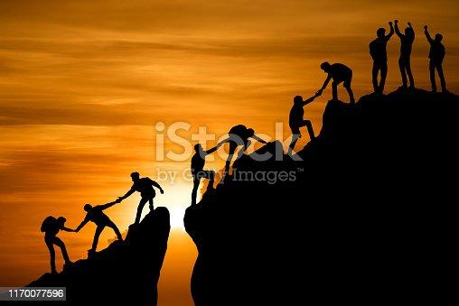 istock Group of people on peak mountain climbing helping team work , travel trekking success business concept 1170077596