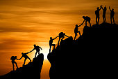 istock Group of people on peak mountain climbing helping team work , travel trekking success business concept 1170077596