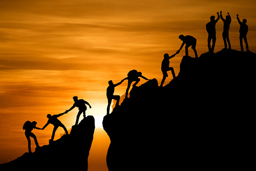 Group Of People On Peak Mountain Climbing Helping Team Work Travel Trekking Success Business Concept Stock Photo - Download Image Now