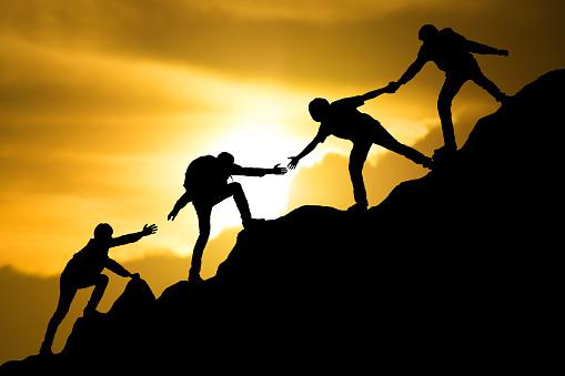istock Group of people on peak mountain climbing helping team work , travel trekking success business concept 955768228