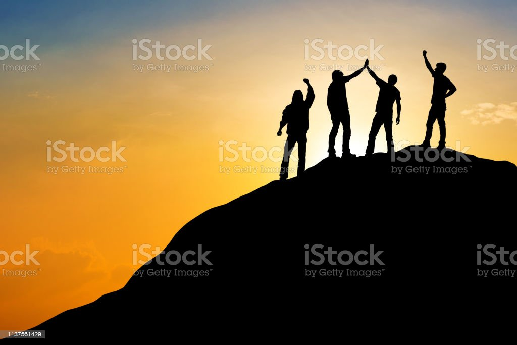 Group of people on peak mountain with sunset background ,team work...