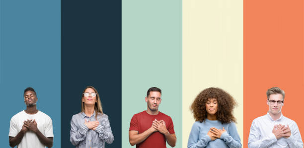 group of people over vintage colors background smiling with hands on chest with closed eyes and grateful gesture on face. health concept. - transparency imagens e fotografias de stock