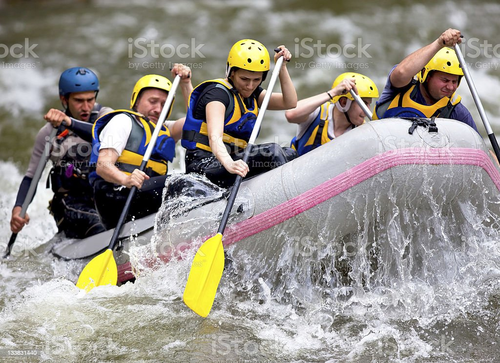 Group of people paddling while whitewater rafting stock photo