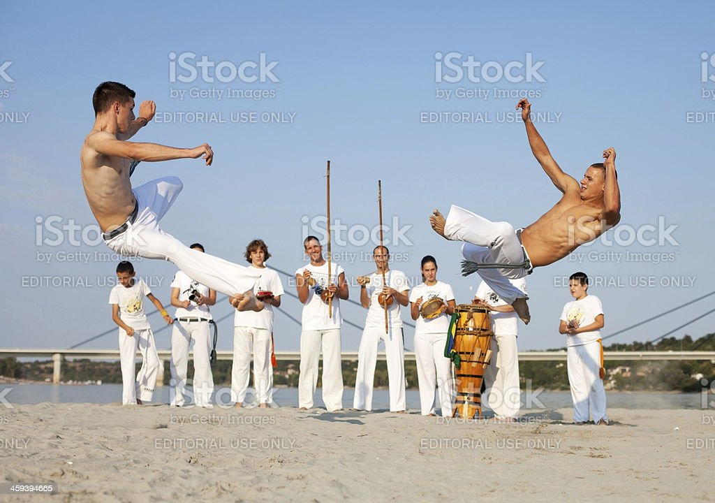 Group of people performing capoeira on the beach. royalty-free stock photo