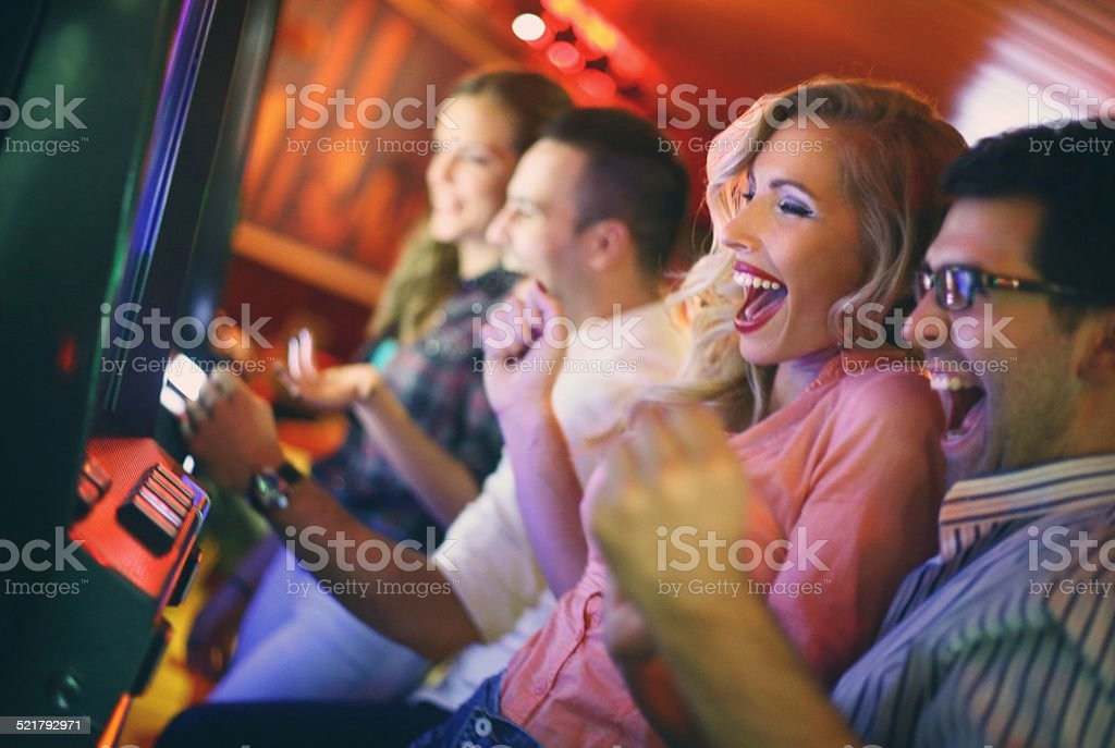 Group of people playing slots in casino. stock photo