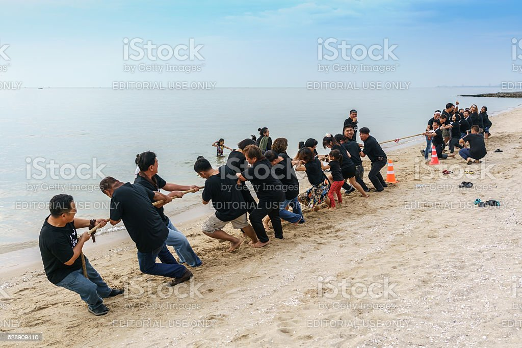 Group of people playing tug of war stock photo