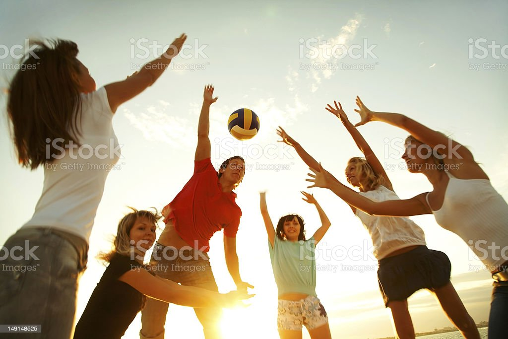 A group of people playing volleyball stock photo