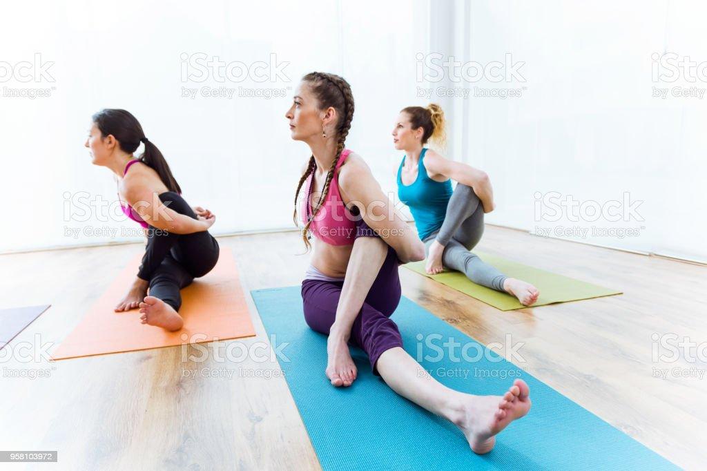 Group of people practicing yoga at home. Marichyasana pose. stock photo
