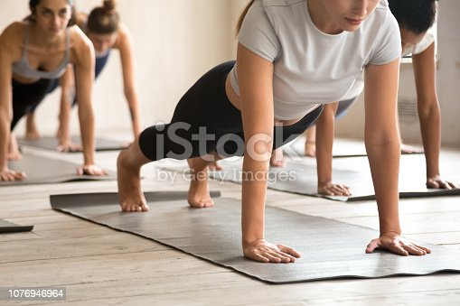 Group of young sporty people practicing yoga, doing Push ups or press ups, Plank exercise, working out indoor close up, active students training at sport club or studio. Well being, fitness concept