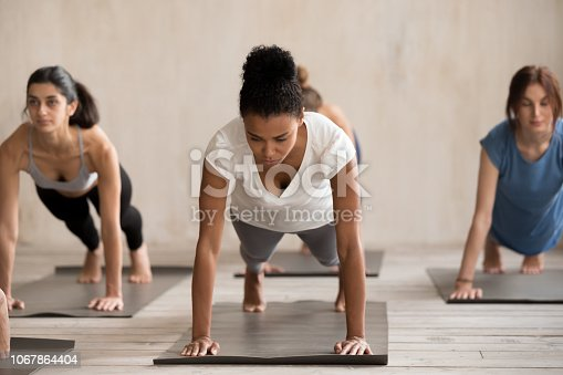 914755448istockphoto Group of people practicing yoga, doing Plank pose 1067864404