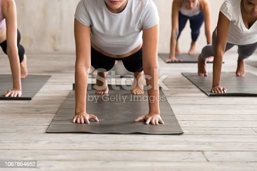 914755448istockphoto Group of people practicing yoga, Plank pose close up 1067864652
