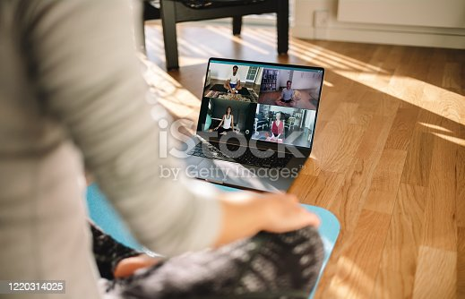 Group of people practicing yoga with trainer via video conference. Fitness coach teaching yoga online to group of people.