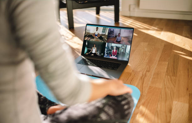Group of people practicing yoga with trainer via video conference stock photo
