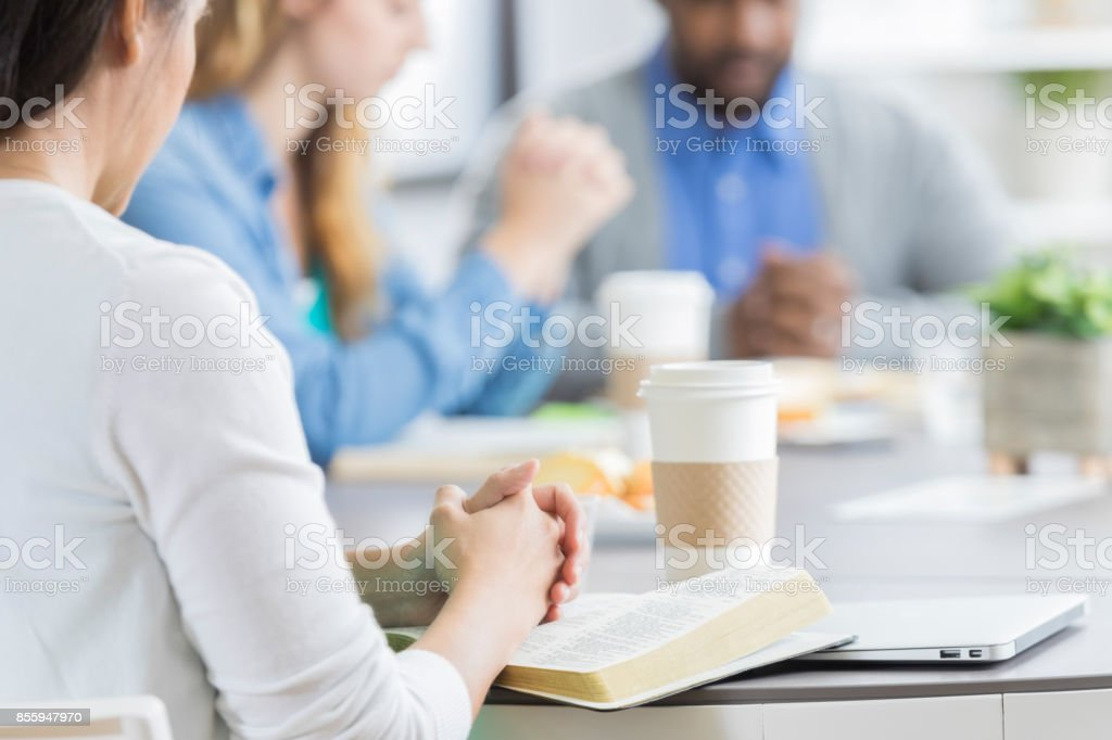 Group of people pray during office Bible study stock photo